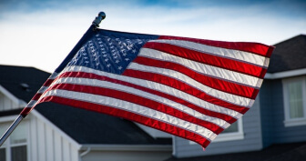 American flag flying from house in residential neighborhood