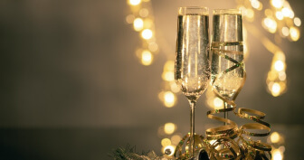 Two Champaign Glasses with Ribbon, Confetti, and Lights